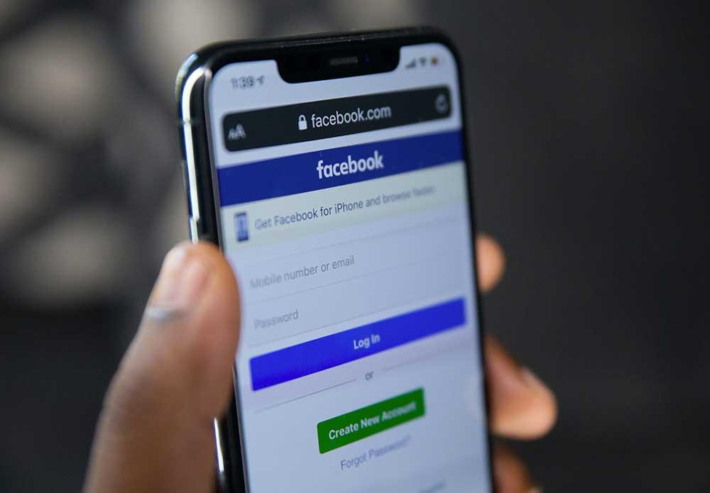 personne tenant un téléphone sur facebook
